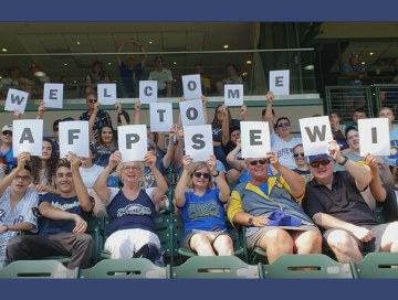 "AFP Members in stands at Brewers baseball game holding cards that spell out ""Welcome to AFPSEWI"""