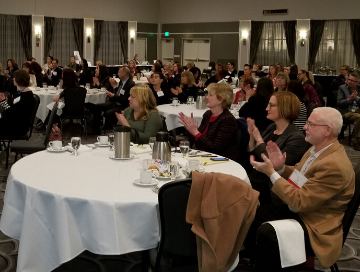image of a dozen luncheon tables with attendees clapping