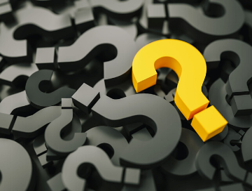 Image of yellow question mark lying atop a pile of black colored question marks