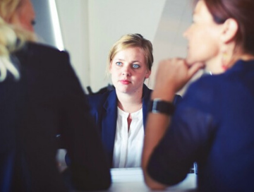 young professional in meeting with two other women