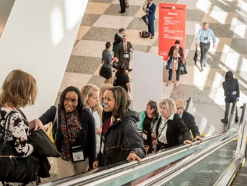 Image of professionals riding up on large escalator in a conference center