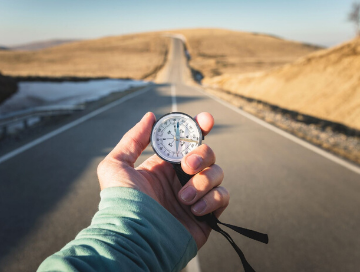 image of person holding compass out in front of them with long road into the desert in front of them