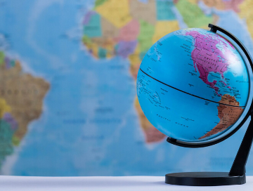 Image of a small globe in the foreground with a wall map in the background