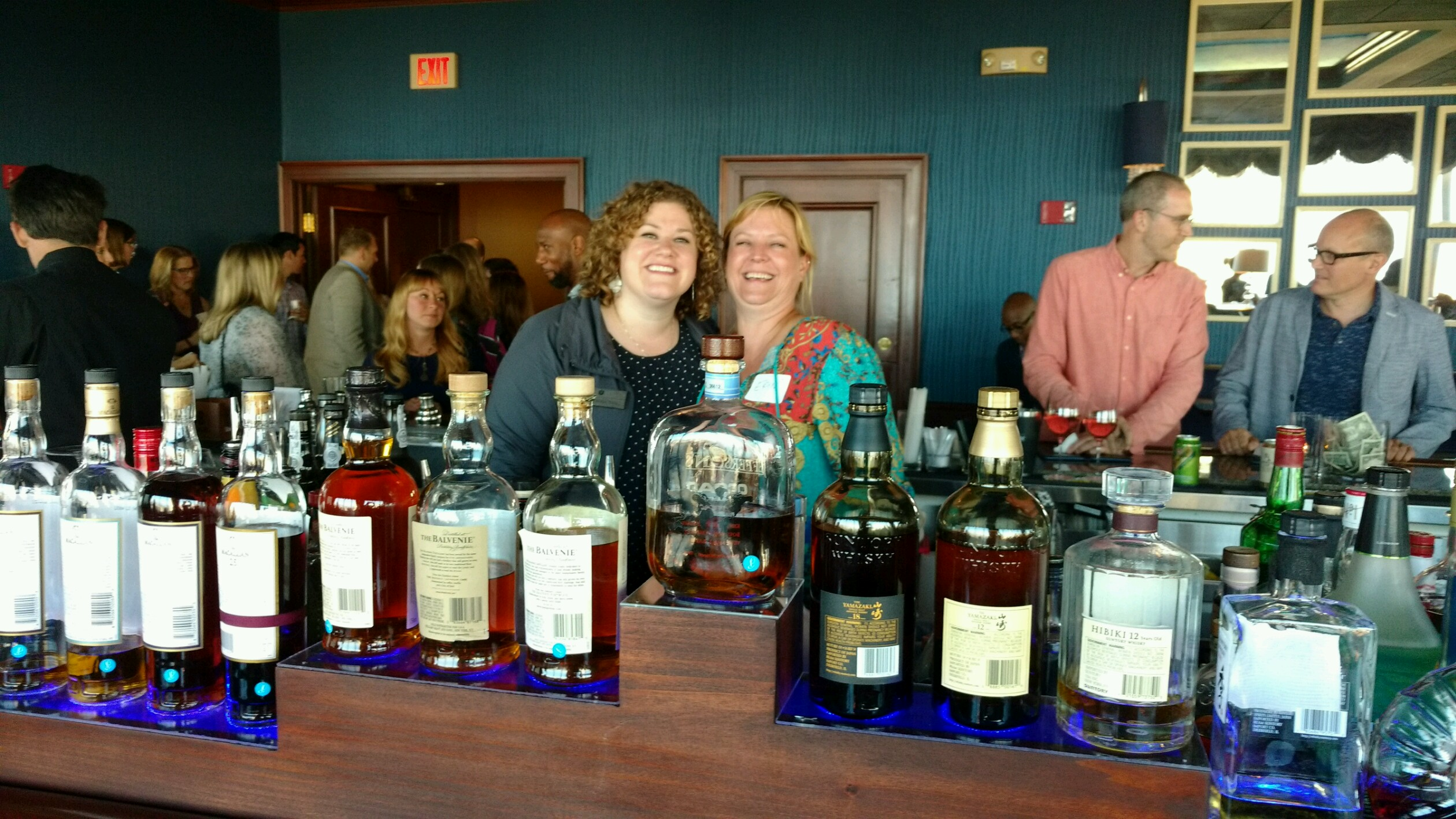 Carolyn Hahn and Erin Richardson posing while bartending. Row of liquor bottles across the bar in the foreground.