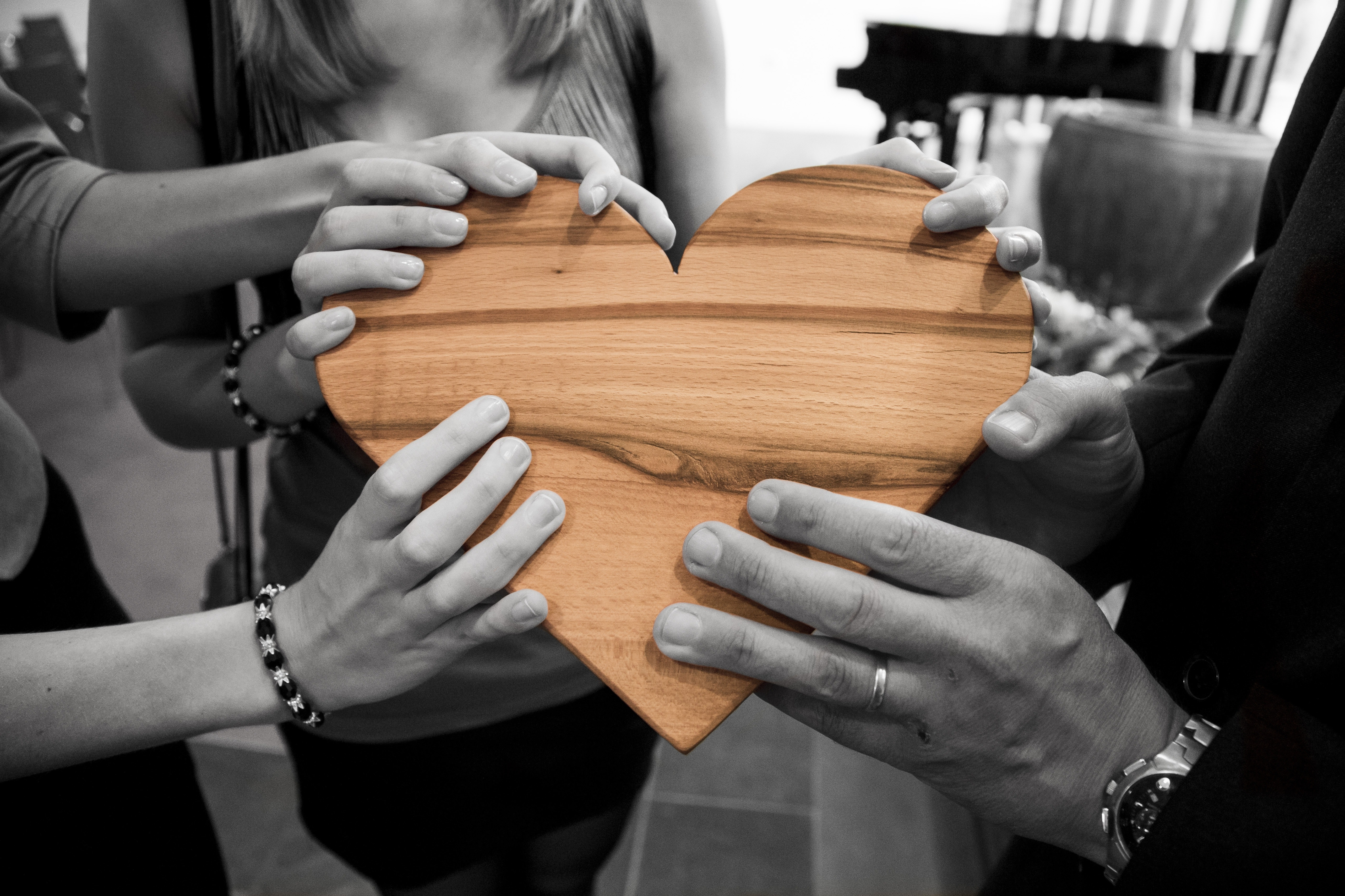 image of several people's hands holding a heart shaped piece of wood