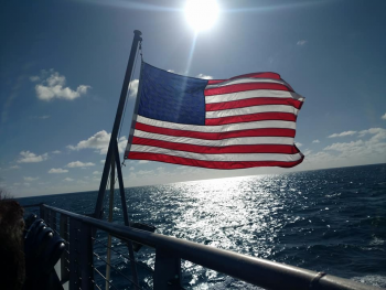 American flag flying on back of a boat with he sun in the background