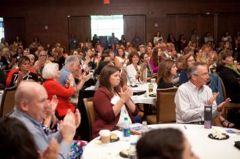 Ballroom of attendees clapping during presentation at FDWI conference in 2018