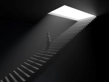 woman walking up underground stairwell toward opening with light coming through
