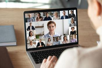 Back view of female employee talk on video call on laptop with diverse colleagues, have group web conference or meeting, woman worker engaged in webcam conversation with coworkers from home