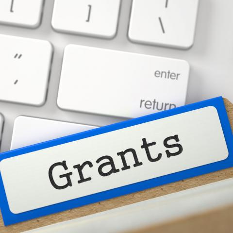 "Keyboard with file folder tab on top labeled ""Grants"""