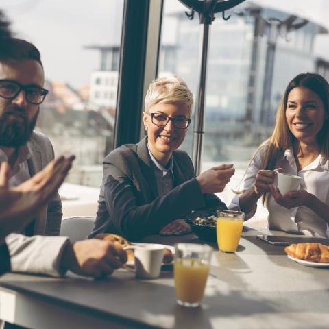 image of four professionals having breakfast meeting