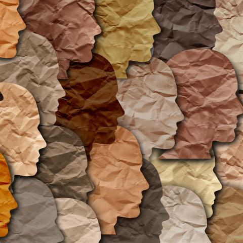 tissue paper cutouts of human head template in a variety of skin tone colors overlapping