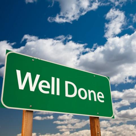 Well done sign with blue cloudy sky behind