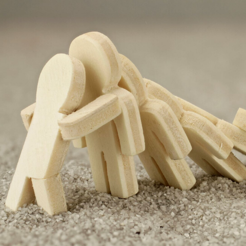 small wood figurines falling like dominoes with the one on the end bracing to stop the next from falling