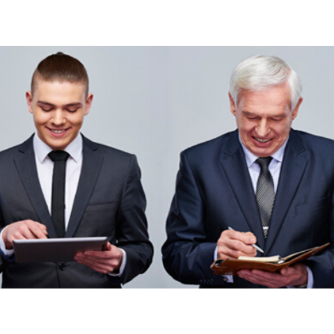 Millennial and seasoned professional both in suits standing together working on their tablet and portfolio