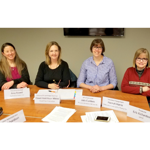 Four new board members seated at conference table