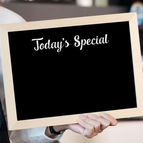 "person holding chalk board sign that says ""Today's Special"""