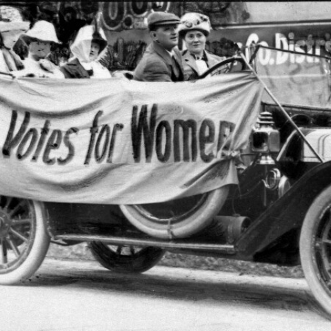 "Photo from 1919 of women in old car with banner that reads ""Votes for Women"""