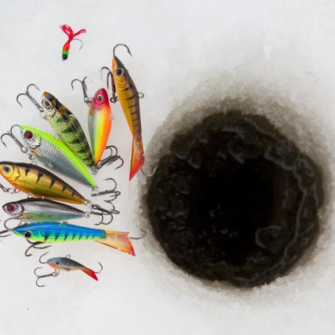 image of ice fishing hole with lures laid out next to it