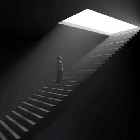 woman standing on stairs underground approaching an opening with light