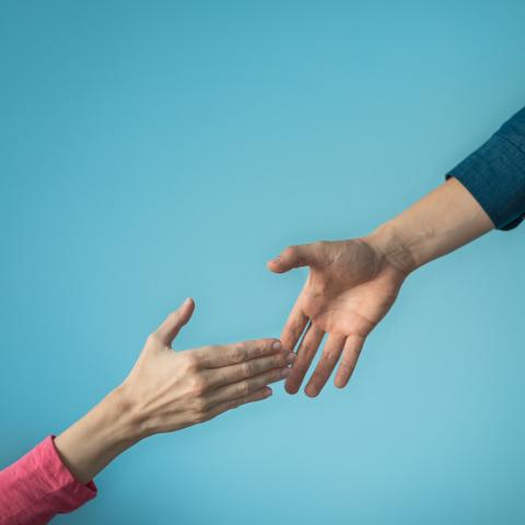 "two female hands reaching for each other depicting a ""helping hand"""