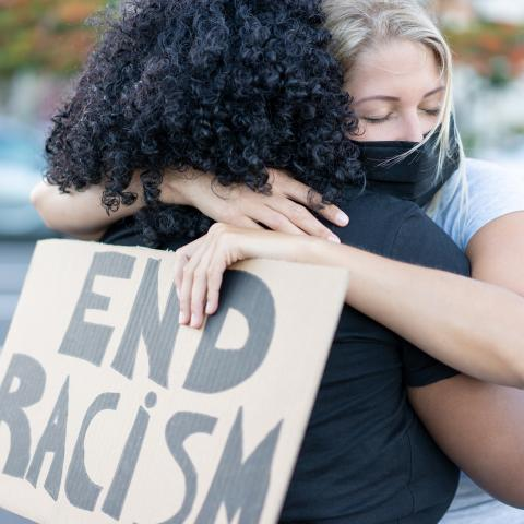 "black and white woman hugging. white women holding a sign that says ""end racism"""