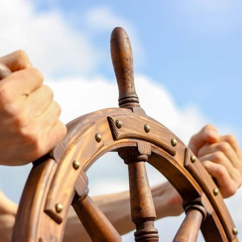 person holding the wooden steering wheel of a ship with blue sky and clouds in the background