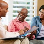Black male professional talking over paperwork with older black couple