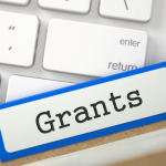 "Labeled file folder ""grants"" resting on a computer keyboard"