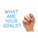 """what are your goals"" written in blue marker with hand next to words holding the marker"