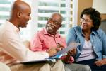 young black professional on a couch visiting with older black couple reviewing documents